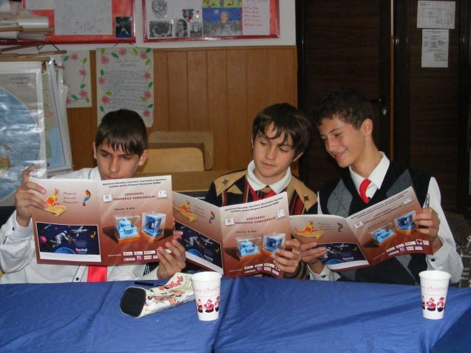 Făgădău Mihai, Stan Mircea și Manea George, elevi ai clasei a VII-a, își confruntă rezultatele.